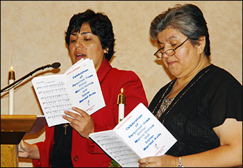 Sisters Marcia and Marisol participate in the singing.