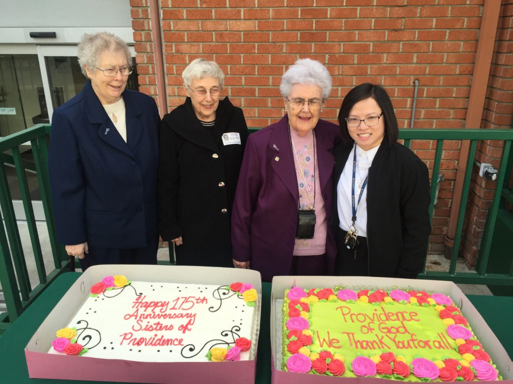 Four Sisters of Providence stand behind a table with two large sheet cakes that say Happy 175th Anniversary Sisters of Providence and Providence of God We Thank You for All.