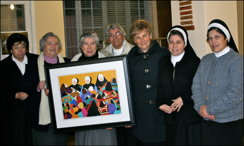 The delegation presents the sisters at the provincial house with a painting by Synthia Saint James.