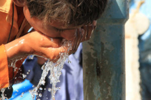 child drinking water from his hands