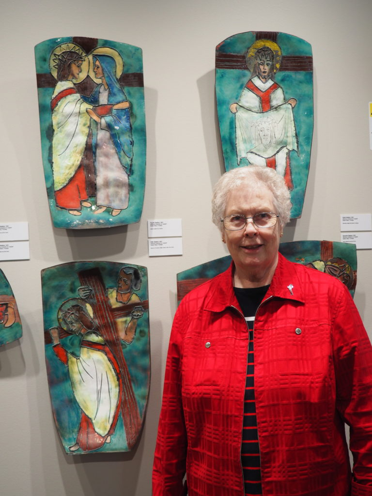 Sister Mary Hawkins stands in front of stations of the cross artwork on a wall