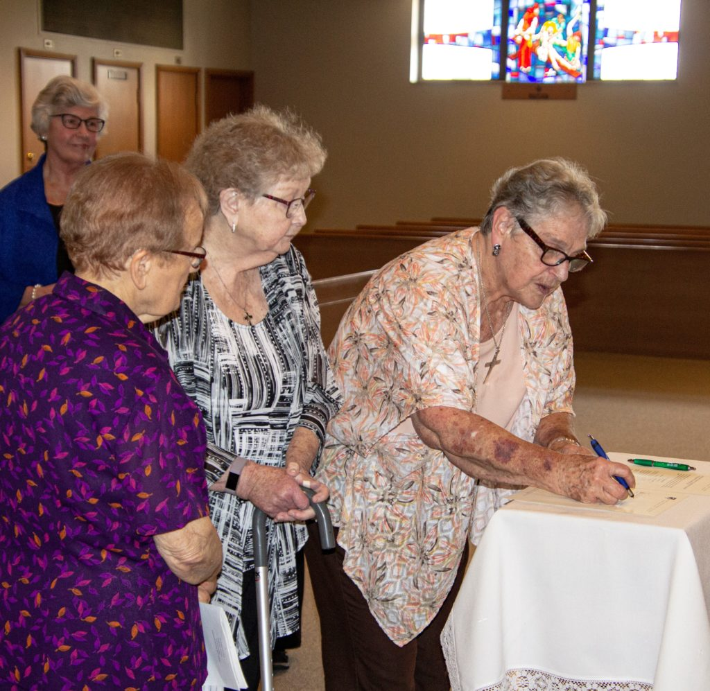 Three religious sisters sign a document on a small table