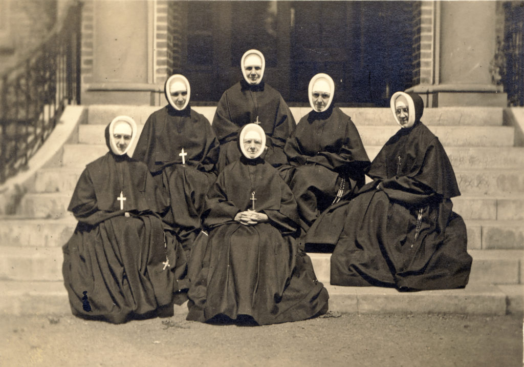 six Sisters of Providence from 1916 are seated on concrete steps in full habit