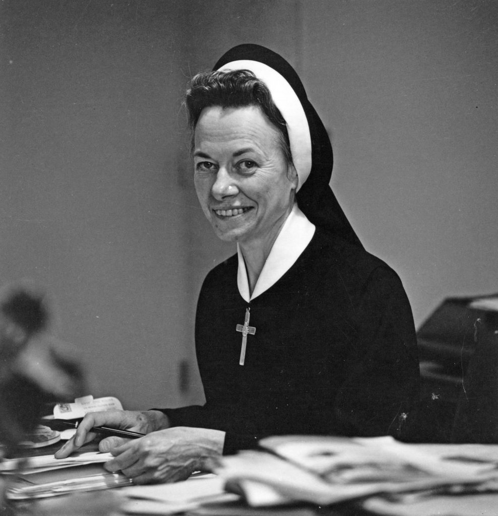 Sr Rita in habit sitting at desk circa 1969