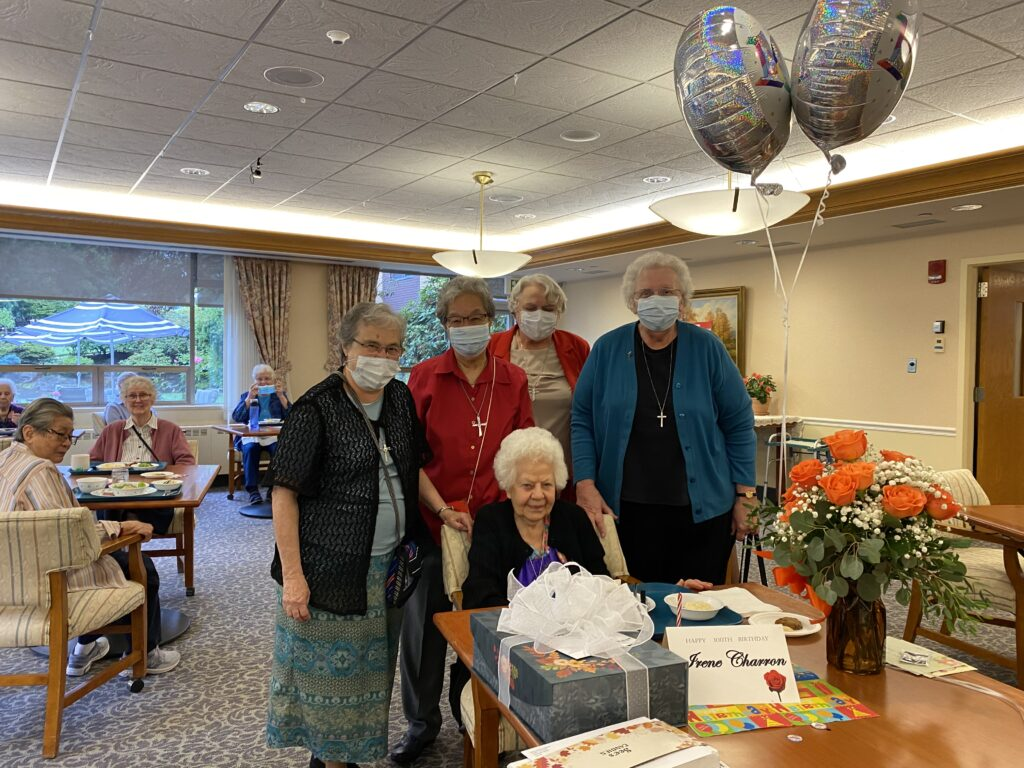 Sister Irene Charron with sisters, cake and gifts on 100th birthday.