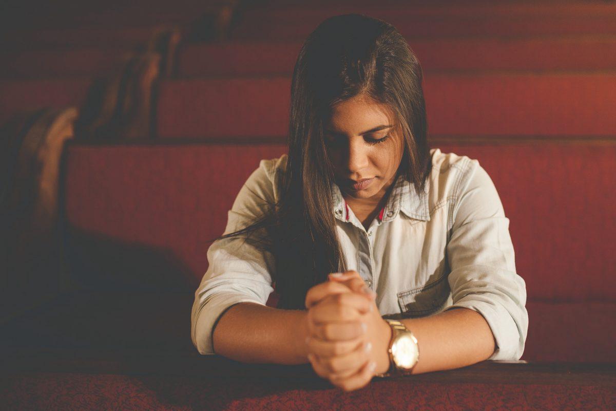 Woman in prayer, kneeling in pews