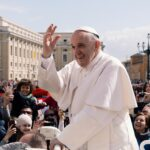 Pope Francis in white outside among people waving to crowd