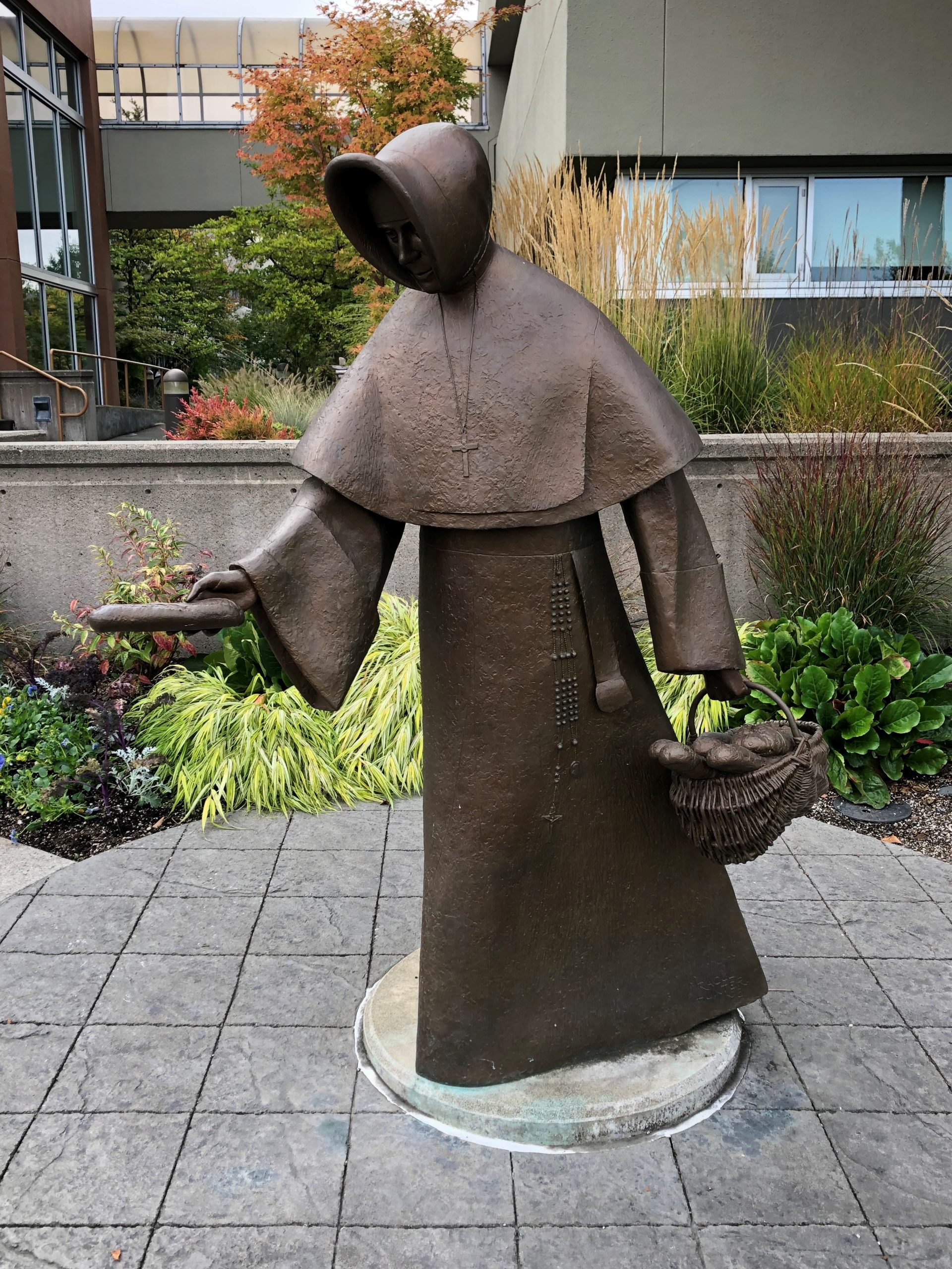 bronze statue of Mother Emilie Gamelin holding out loaf of bread