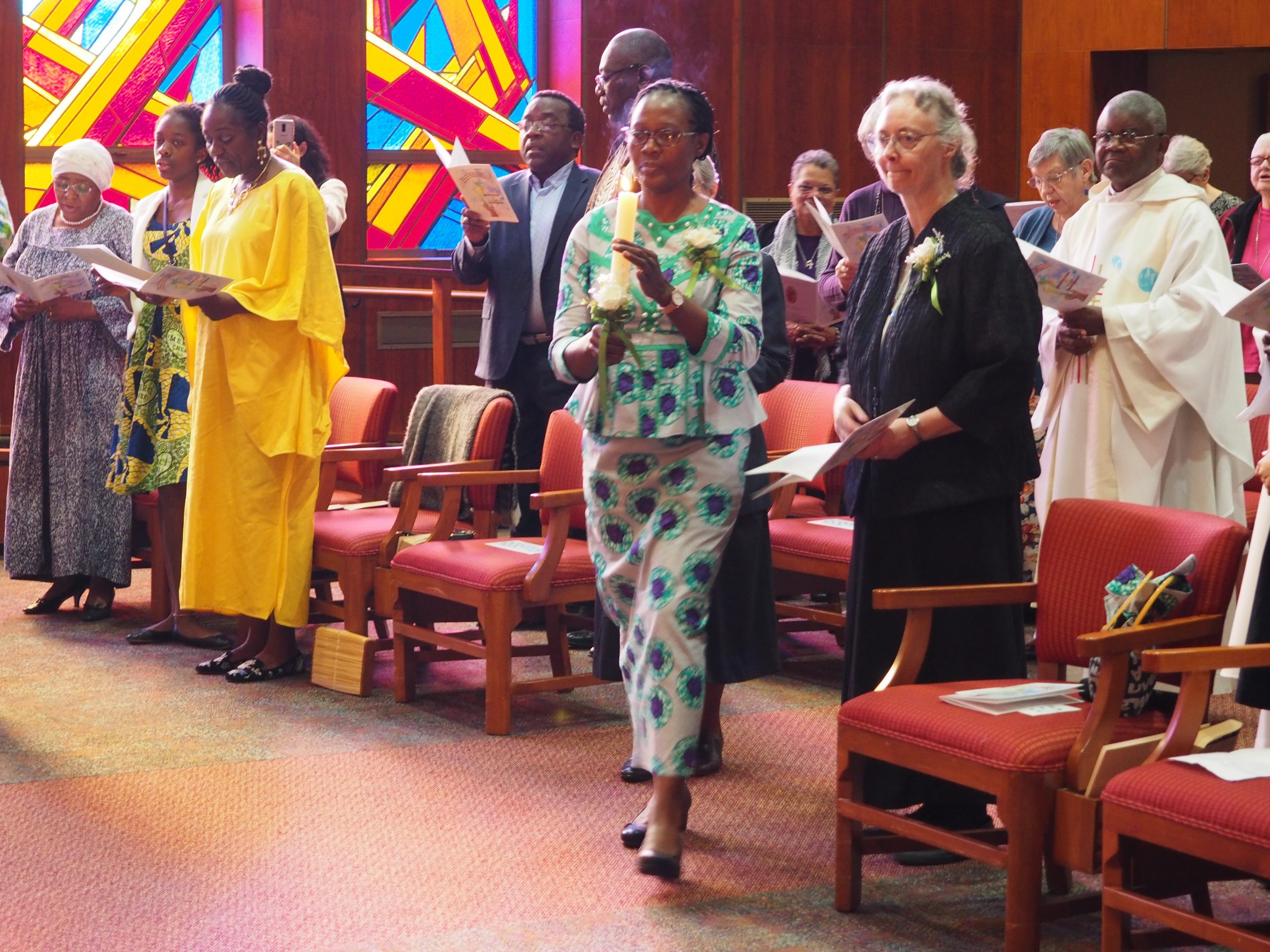 Sisters, priest and guests in a chapel.
