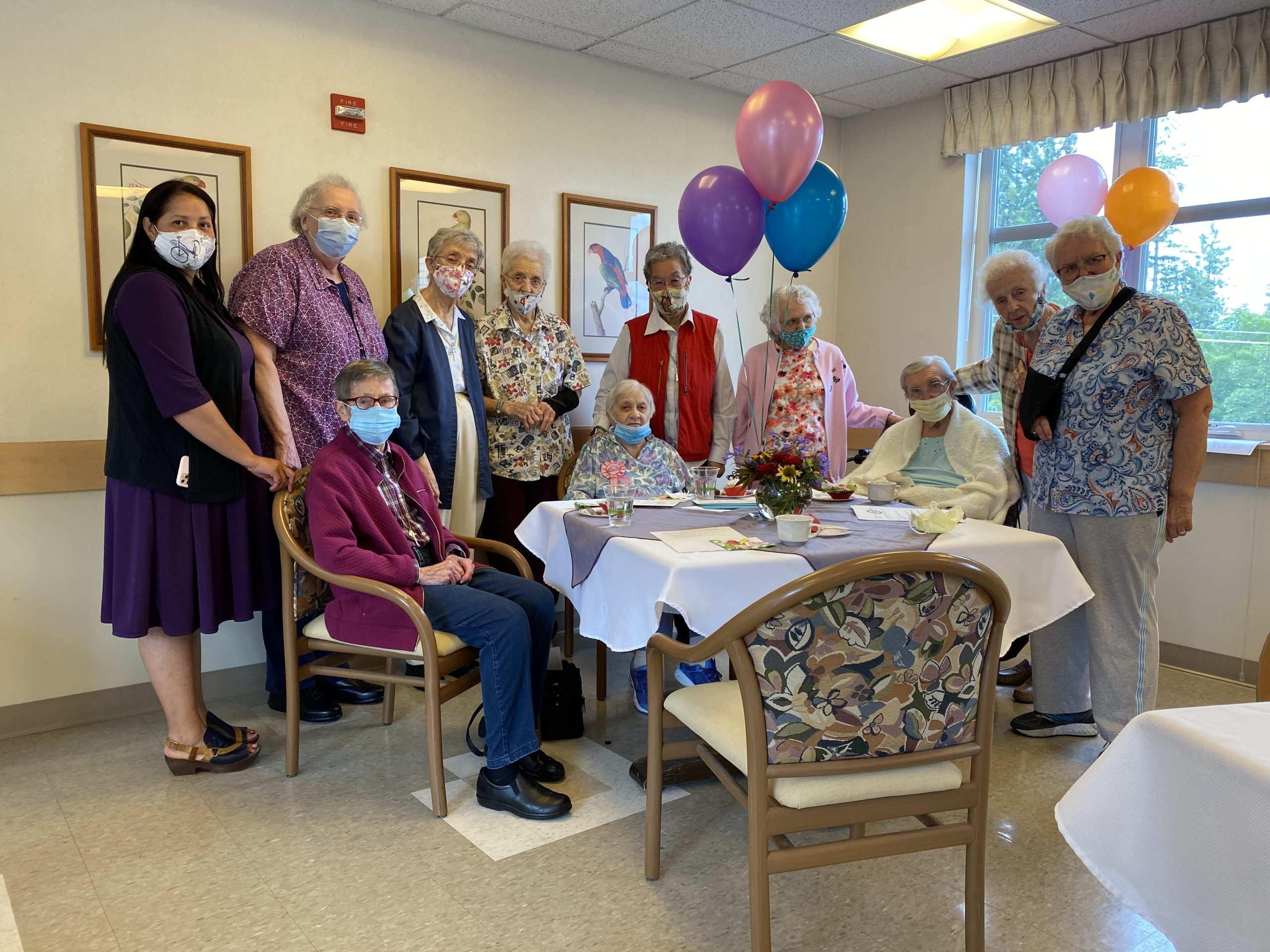 Sr Cecilia Paganessi surrounded by sisters with balloons and treats for 100th birthday