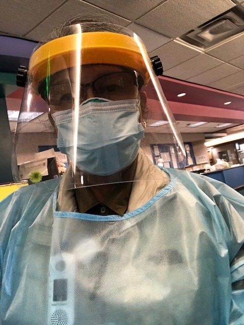 Sr Fe, hospital chaplain, in personal protective equipment (gown, ask, face shield)