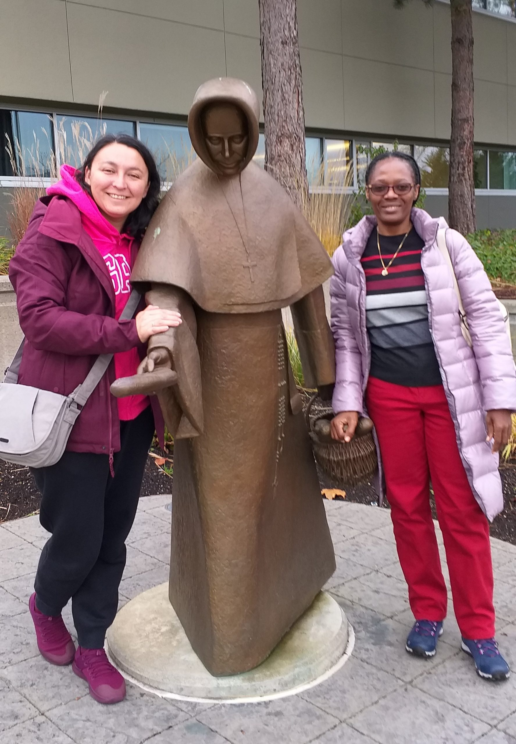 Srs Maria Fernanda and Marie-Therese flank bronze statue of Blessed Emilie Gamelin.