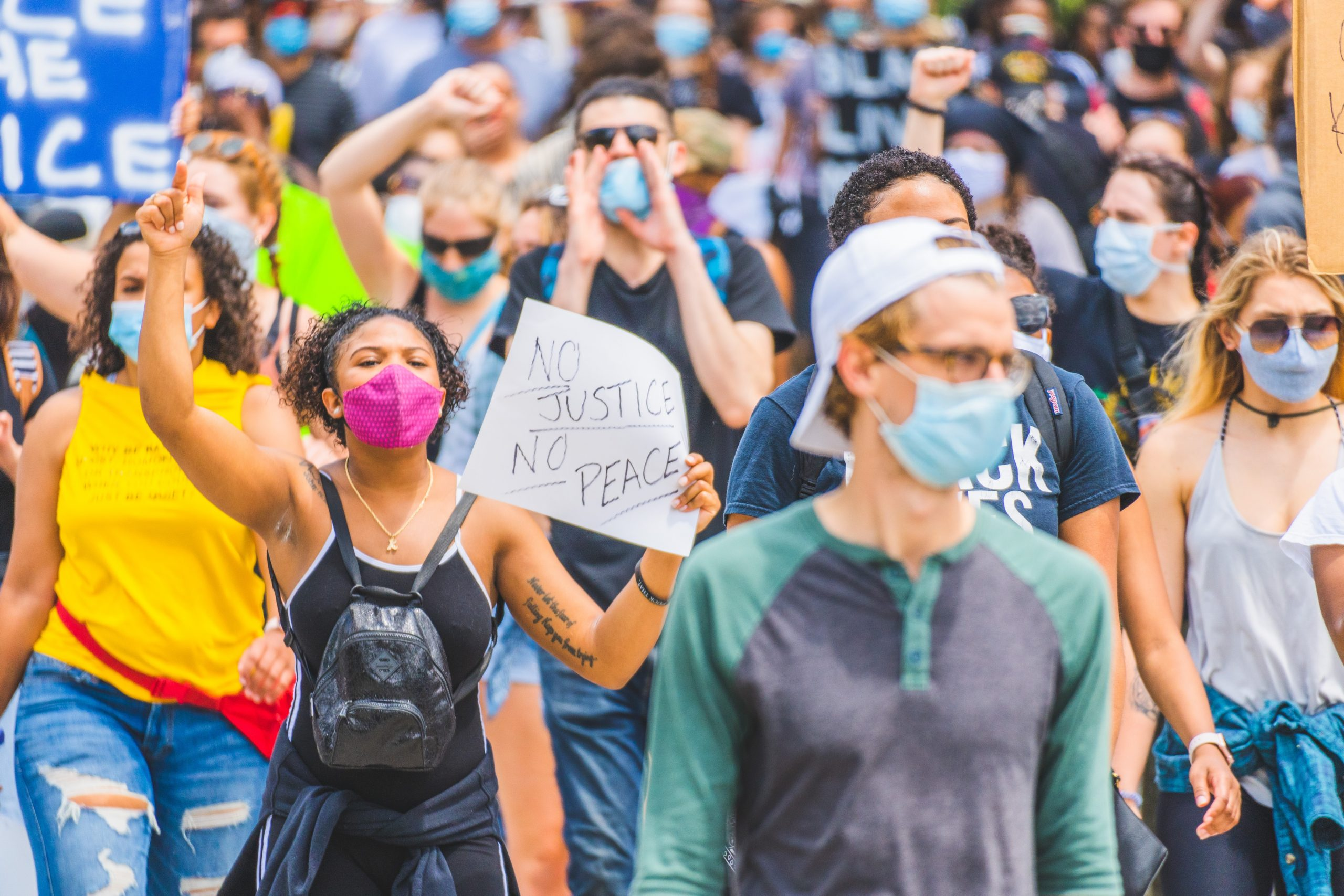 demonstrators wearing masks and carrying signs