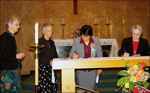 Sister Marita signs documents