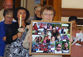 Sister Lily May Emert carries photo collage representing Sister Vilma's friends and family