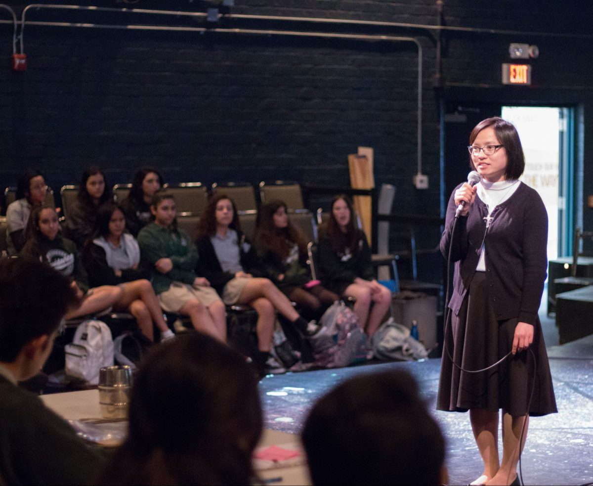 Sr Rosa in modified habit on a stage speaking into mic to a group of high school students
